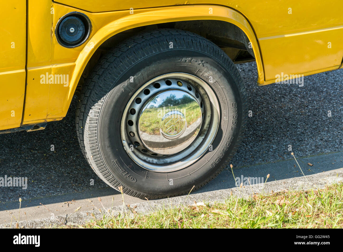 Regensburg, Bavaria, Germany – July 18, 2016: The picture shows a closeup of a chrome felloe on a yellow VW Bus - Stock Image