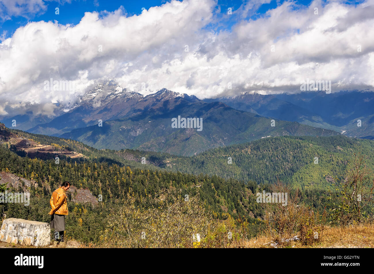 Middle aged mature adult Bhutanese man in traditional dress standing beside rock looking into mountains with copy - Stock Image