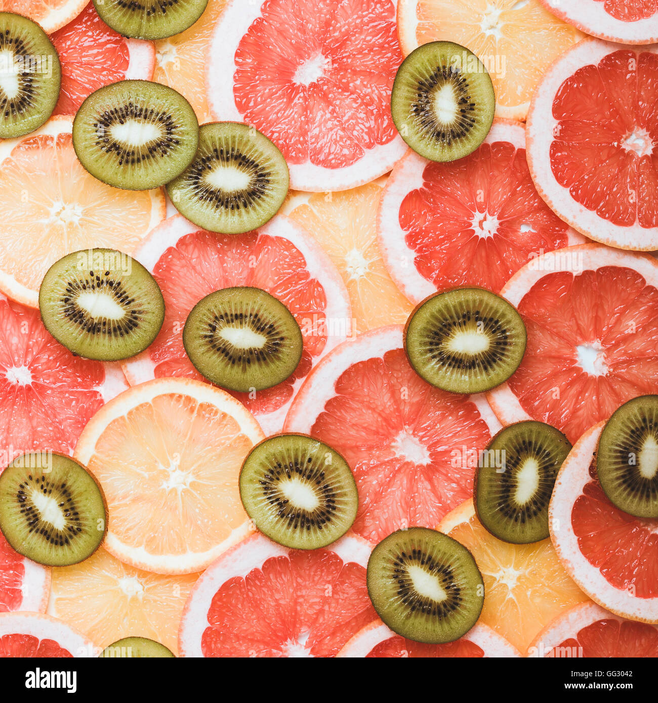 Fresh citrus fruits slices background viewed from above. Grapefruit, orange, kiwi pattern - Stock Image