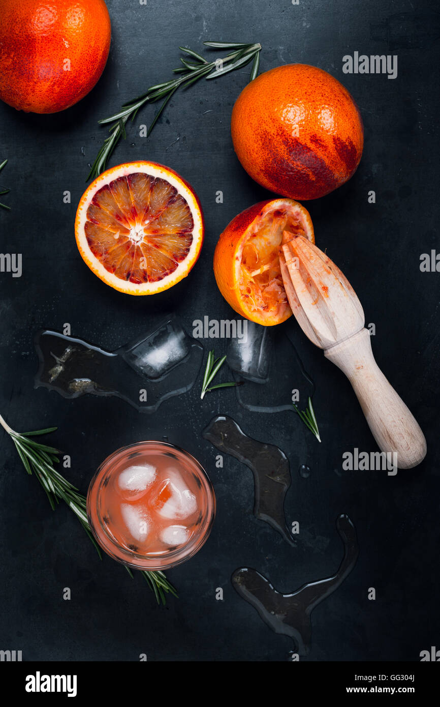 Fresh squeezed juice and blood oranges on gray background, top view - Stock Image