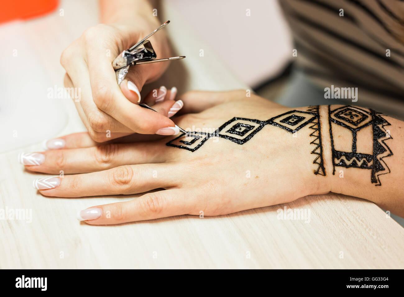 Artist applying henna tattoo on women hands. Mehndi is