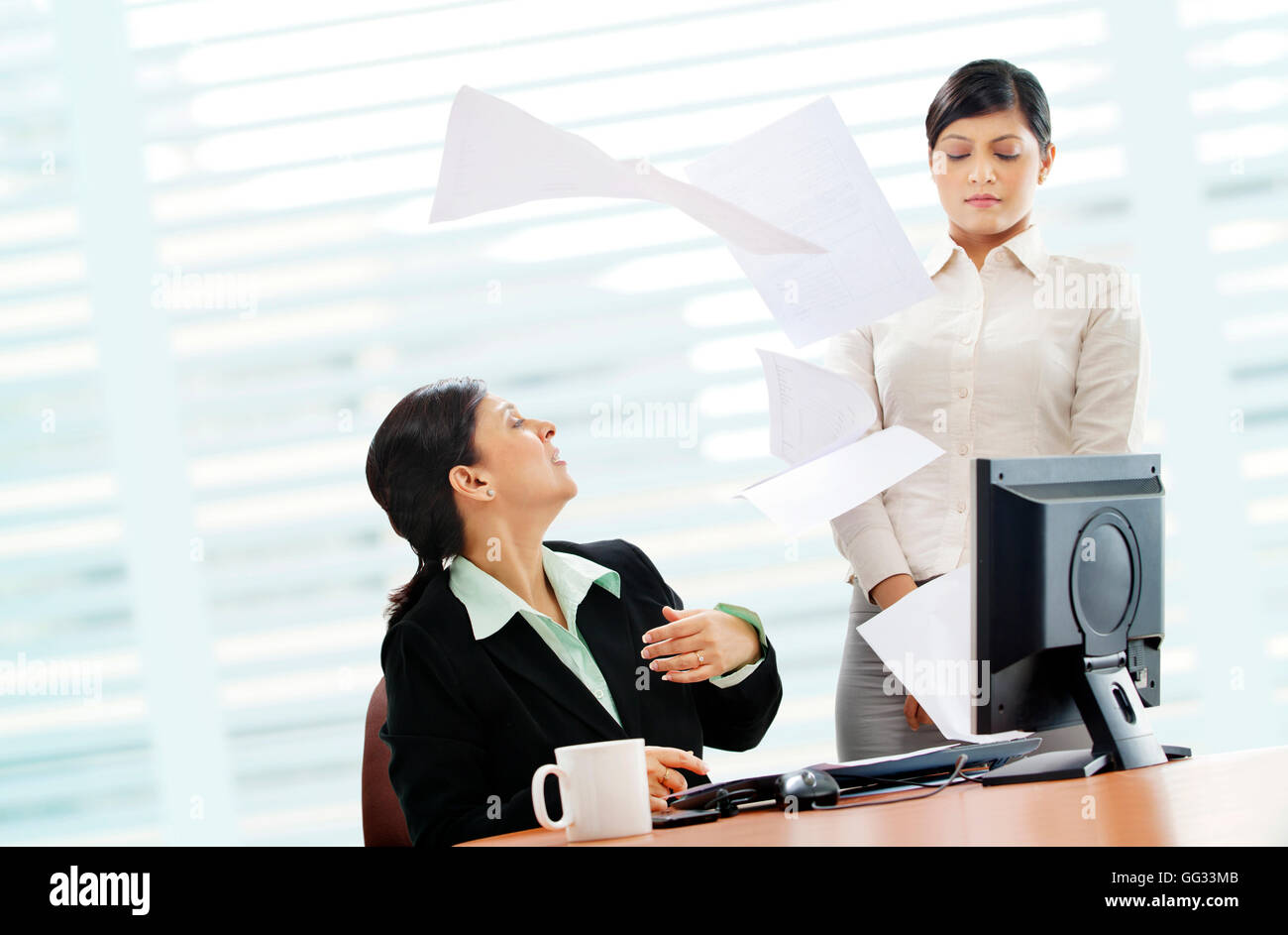 Furious mature businesswoman throwing papers on female executive - Stock Image