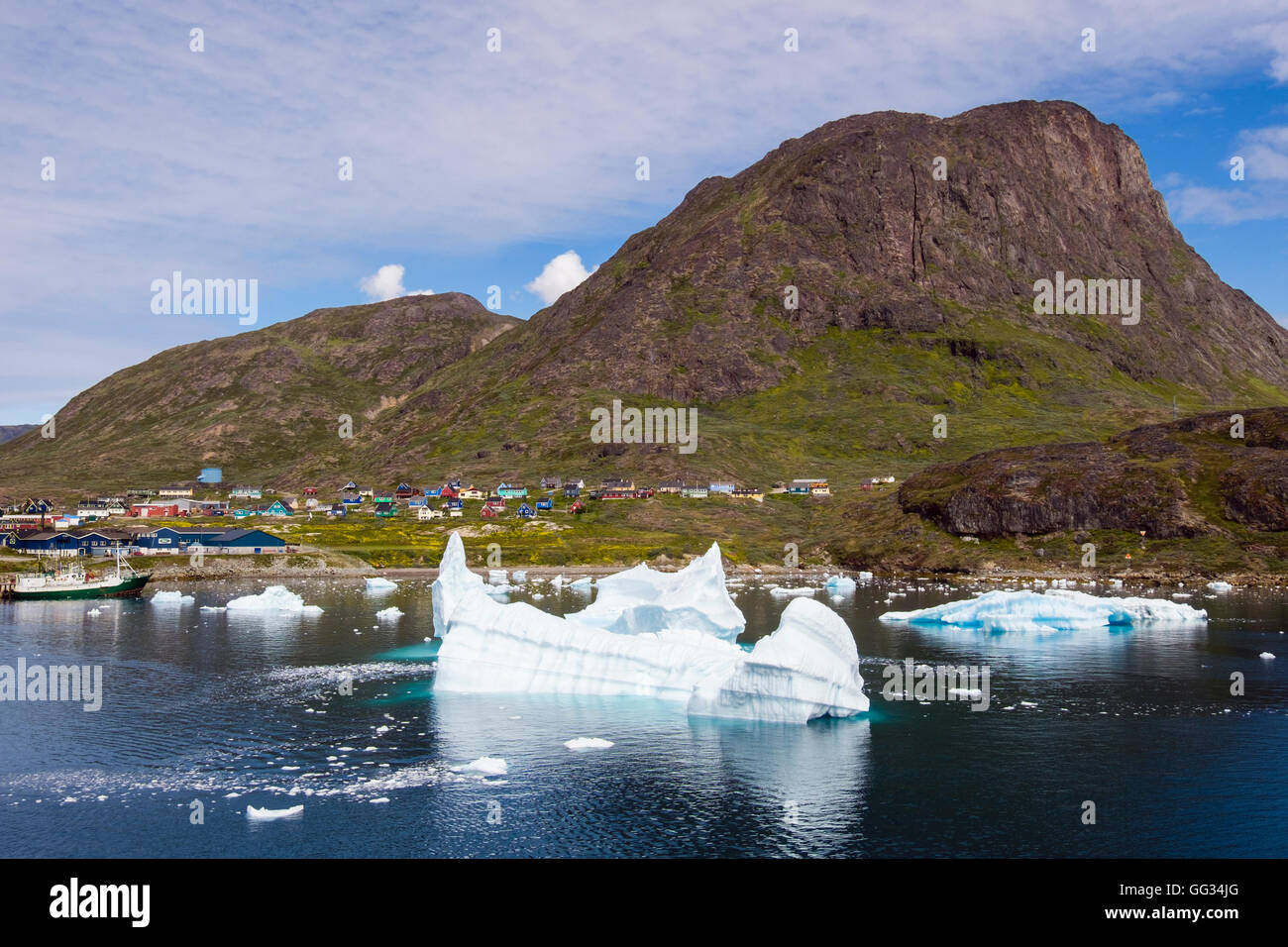 Icebergs from Tunulliarfik fjord floating offshore with view to town below Qaqqarsuaq Fjeld mountain. Narsaq Kujalleq - Stock Image