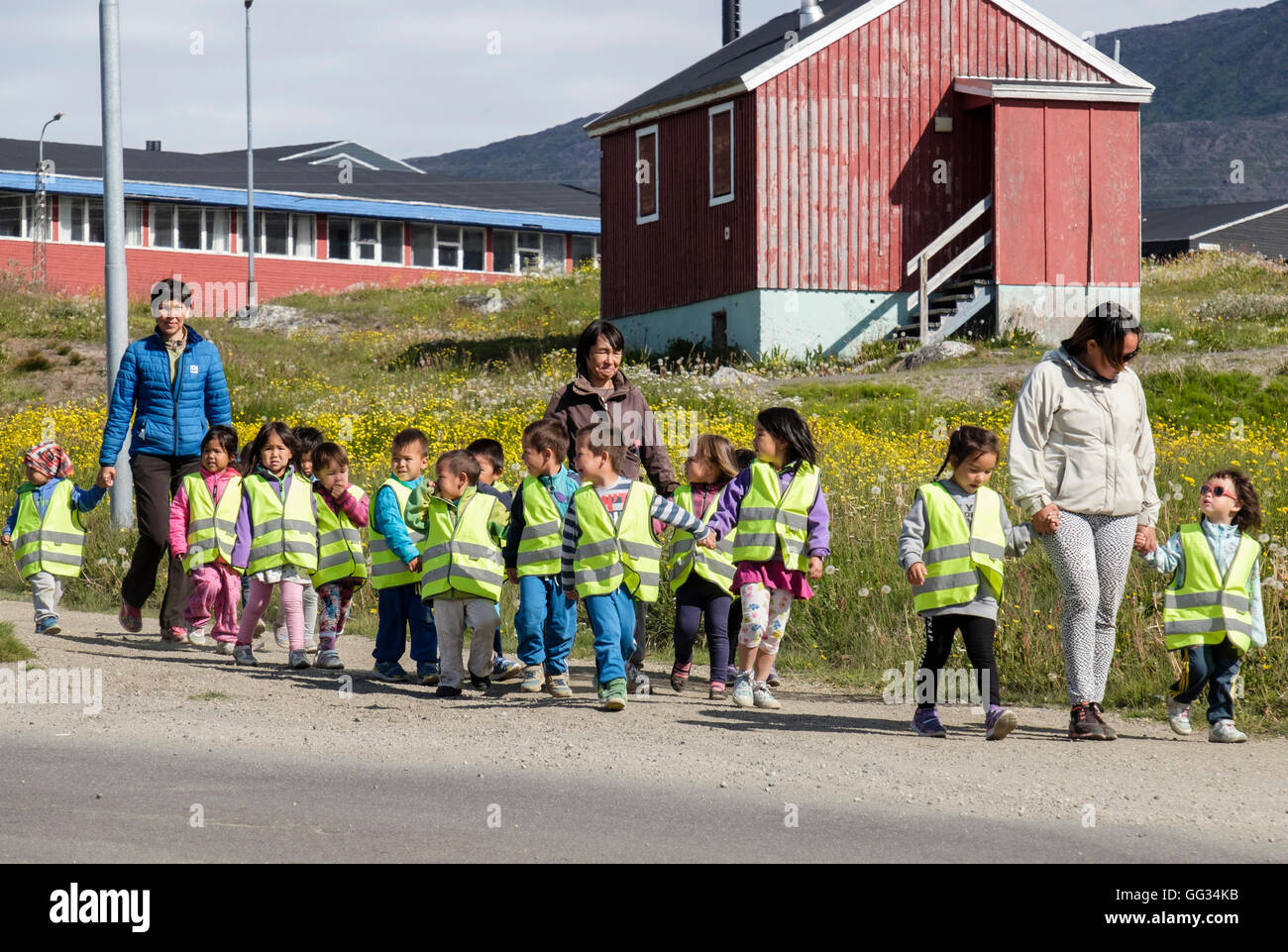 Local school children wearing hi-vis jackets and holding hands walking along a street with their teachers in summer - Stock Image