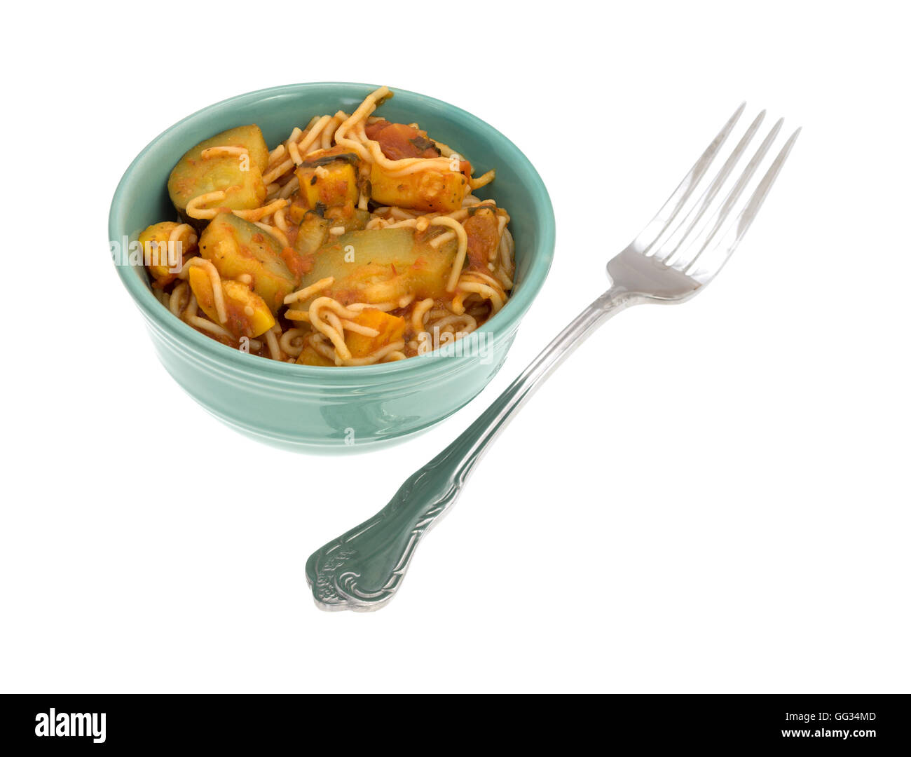 TV dinner of angel hair pasta with zucchini and spinach in a small green bowl with a fork to the side on a white - Stock Image