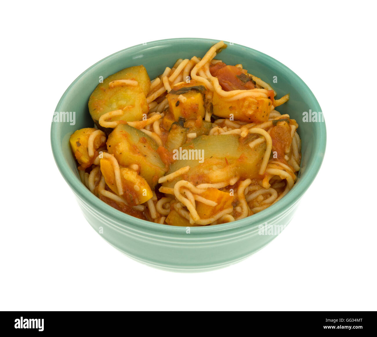 TV dinner of angel hair pasta with zucchini and spinach in a small green bowl on a white background. - Stock Image