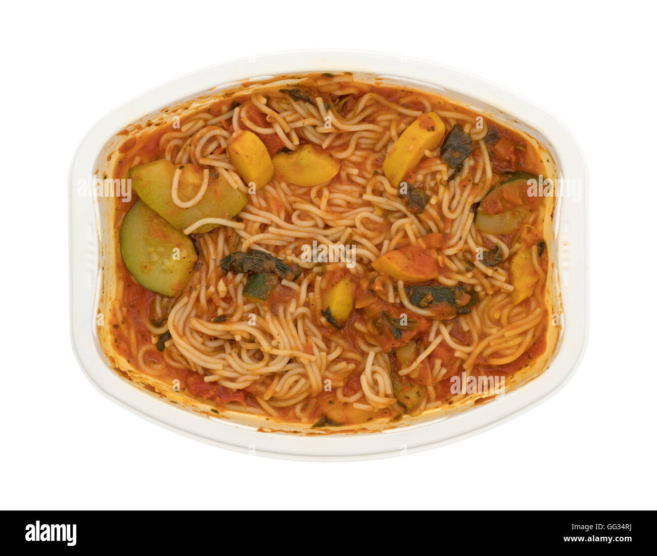 A cooked TV dinner of angel hair pasta with zucchini and spinach in a microwaveable tray on a white background. - Stock Image