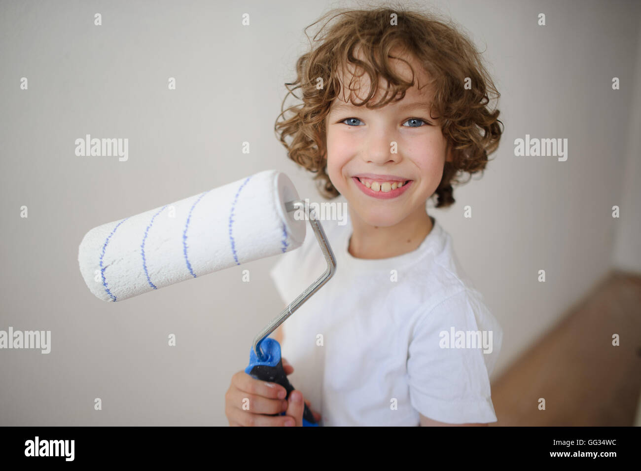 Cheerful boy with a roller to paint in his hands. Curly lad 8-9 years, standing near a white wall. He looks at the - Stock Image