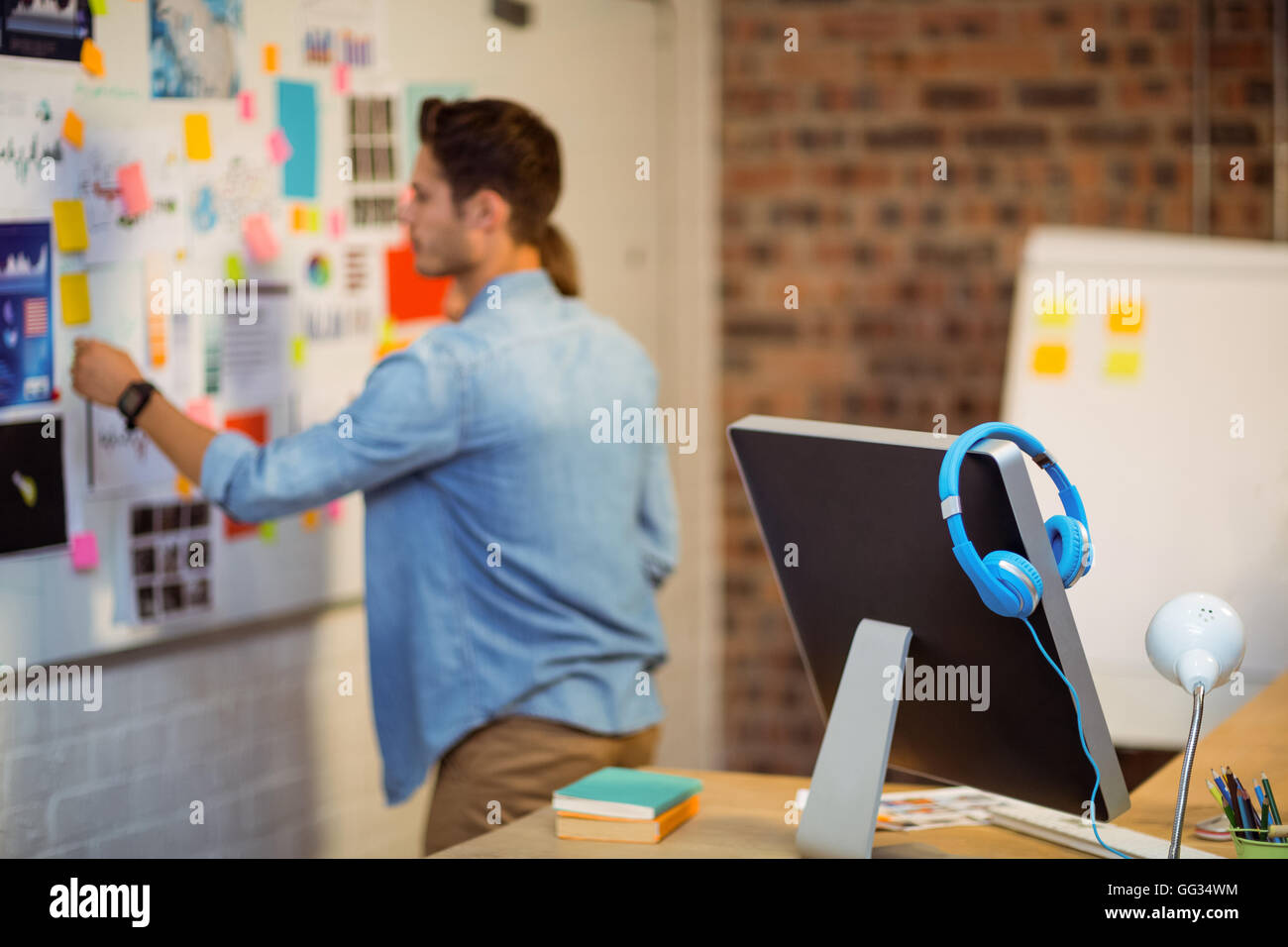 Business executive putting sticky notes on whiteboard - Stock Image