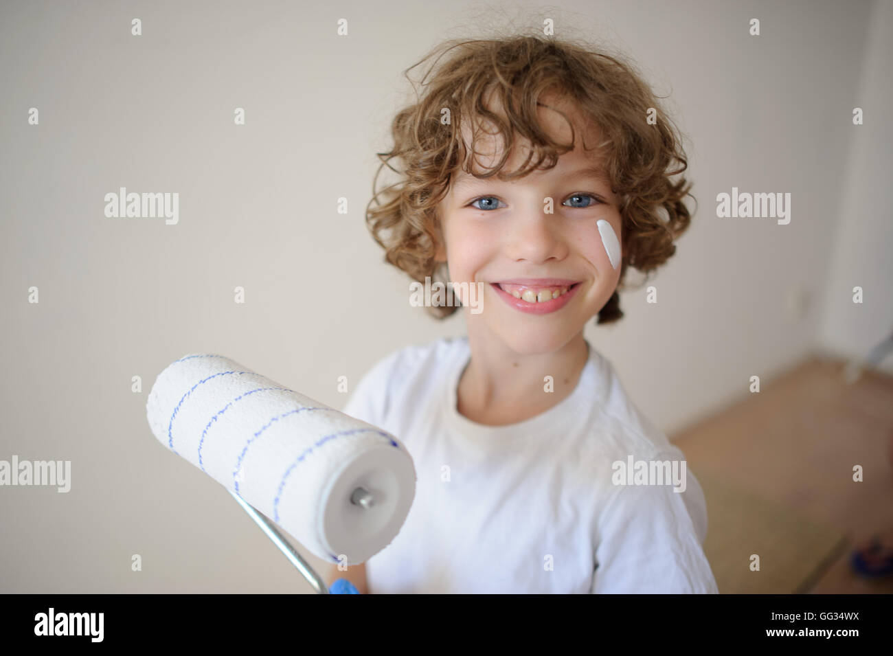 Cute little boy holding a roller for painting. His cheek was smeared with white paint. A boy with a cheerful smile, - Stock Image
