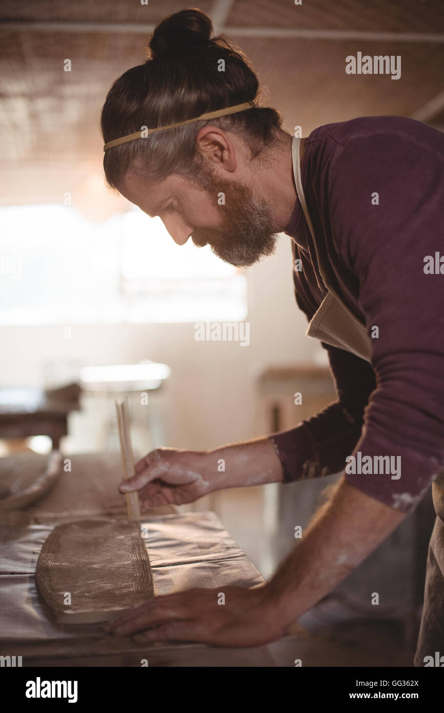 Male potter designing clay with sticks - Stock Image