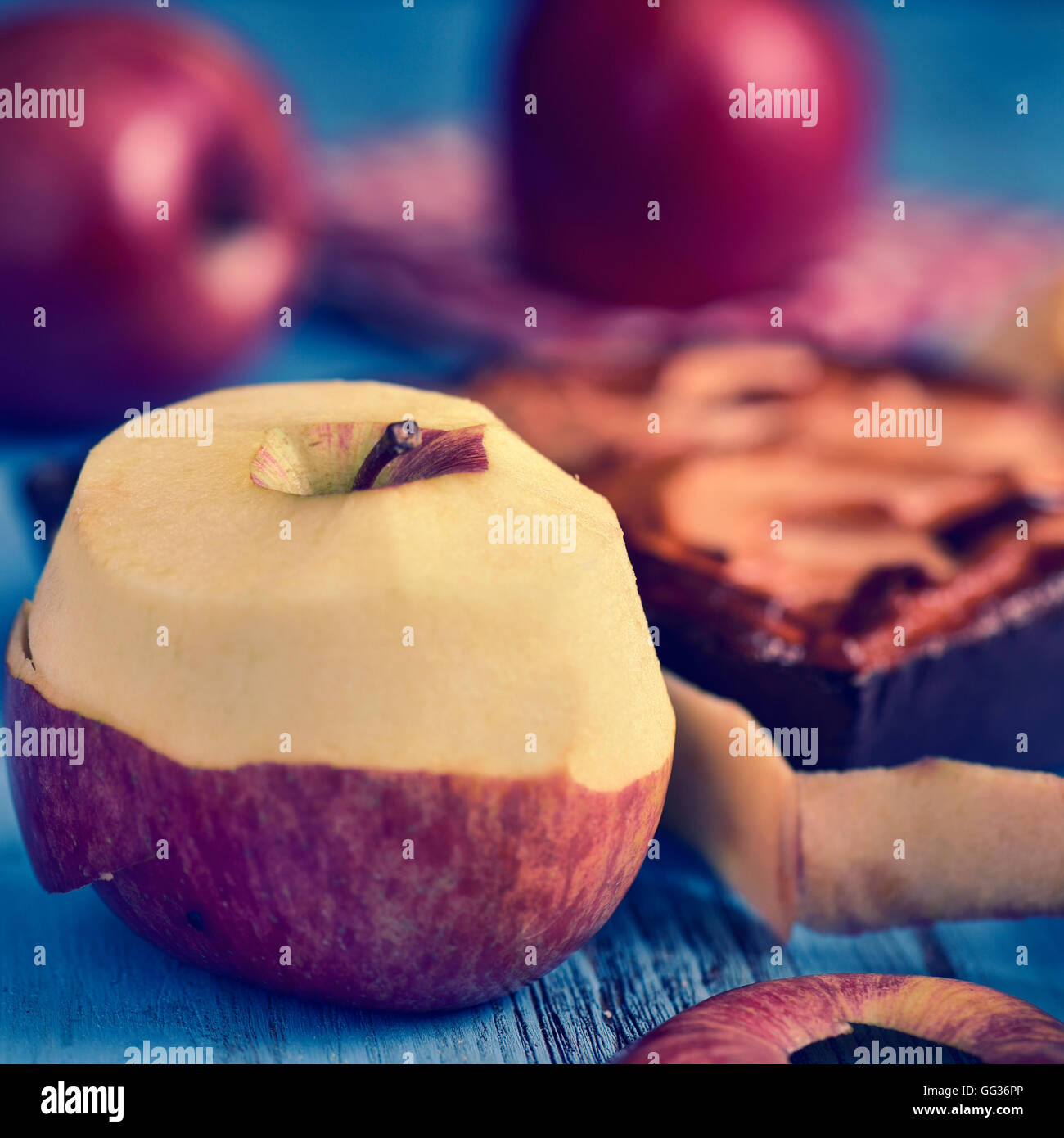closeup of an apple cake and some red apples on a blue rustic wooden table, with a filter effect - Stock Image