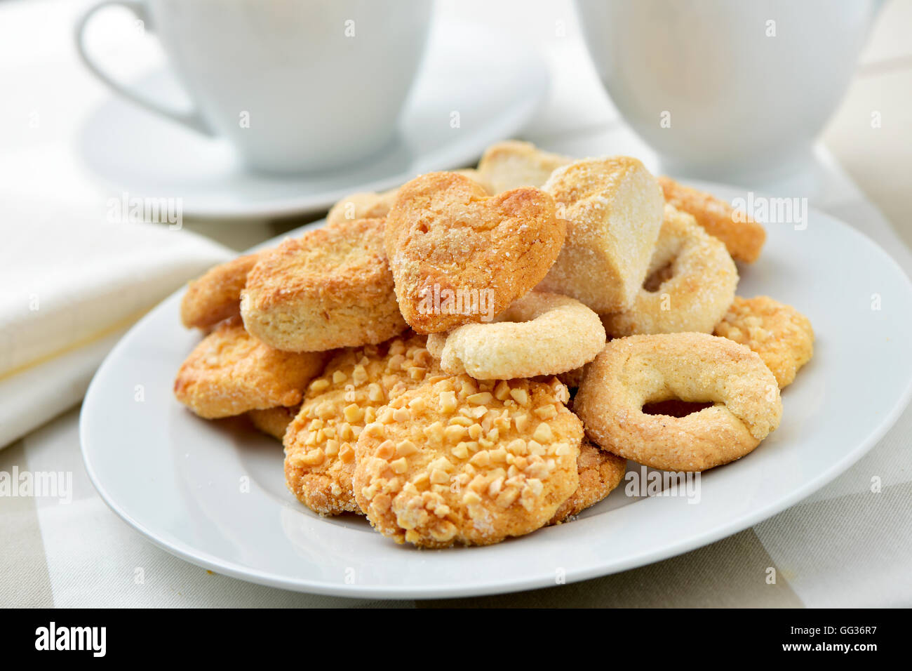 closeup of an assortment of different shortbread biscuits in a white plate, on a set table with some cups of tea - Stock Image