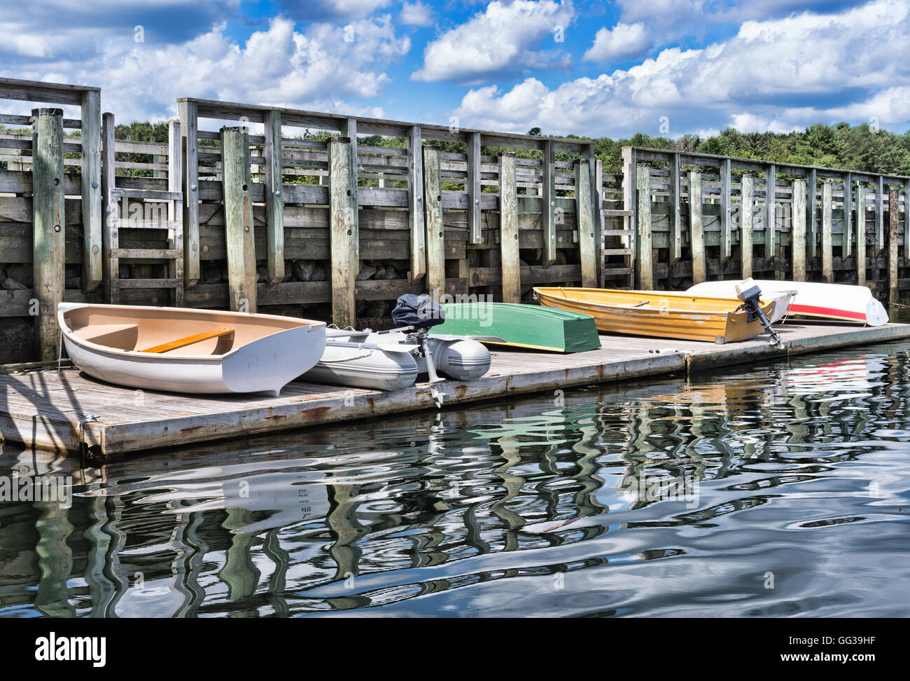 Several wood and rubber skiffs with motors on a floating dock at Searsport, Maine - Stock Image