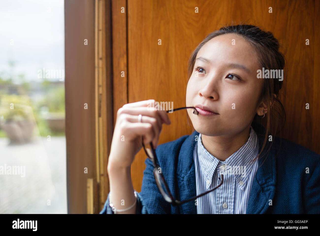 Thoughtful young woman looking through window - Stock Image