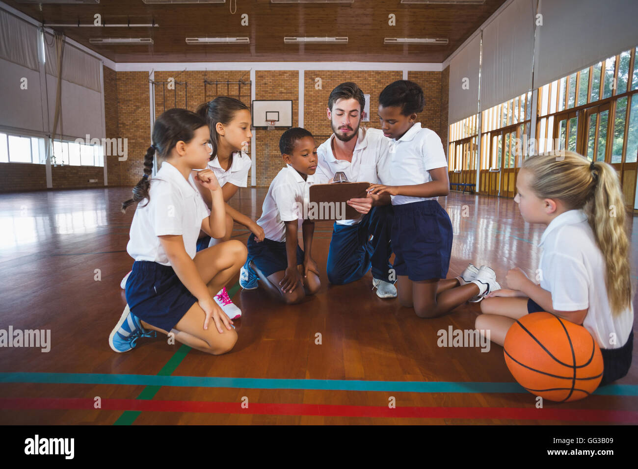 Sport teacher and school kids discussing on clipboard in basketball court - Stock Image