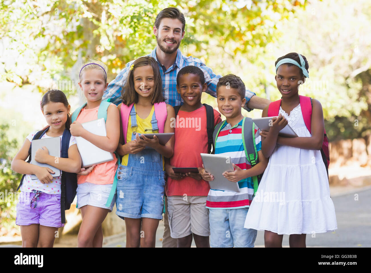 Teacher standing with school kids - Stock Image