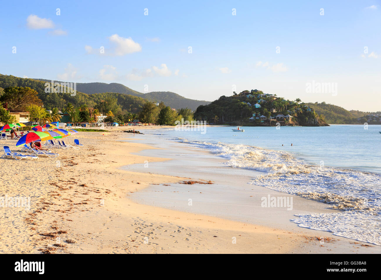 Antiguan landscape and sightseeing: Golden sand, blue sky and colourful beach umbrellas at Jolly Harbour on a sunny - Stock Image