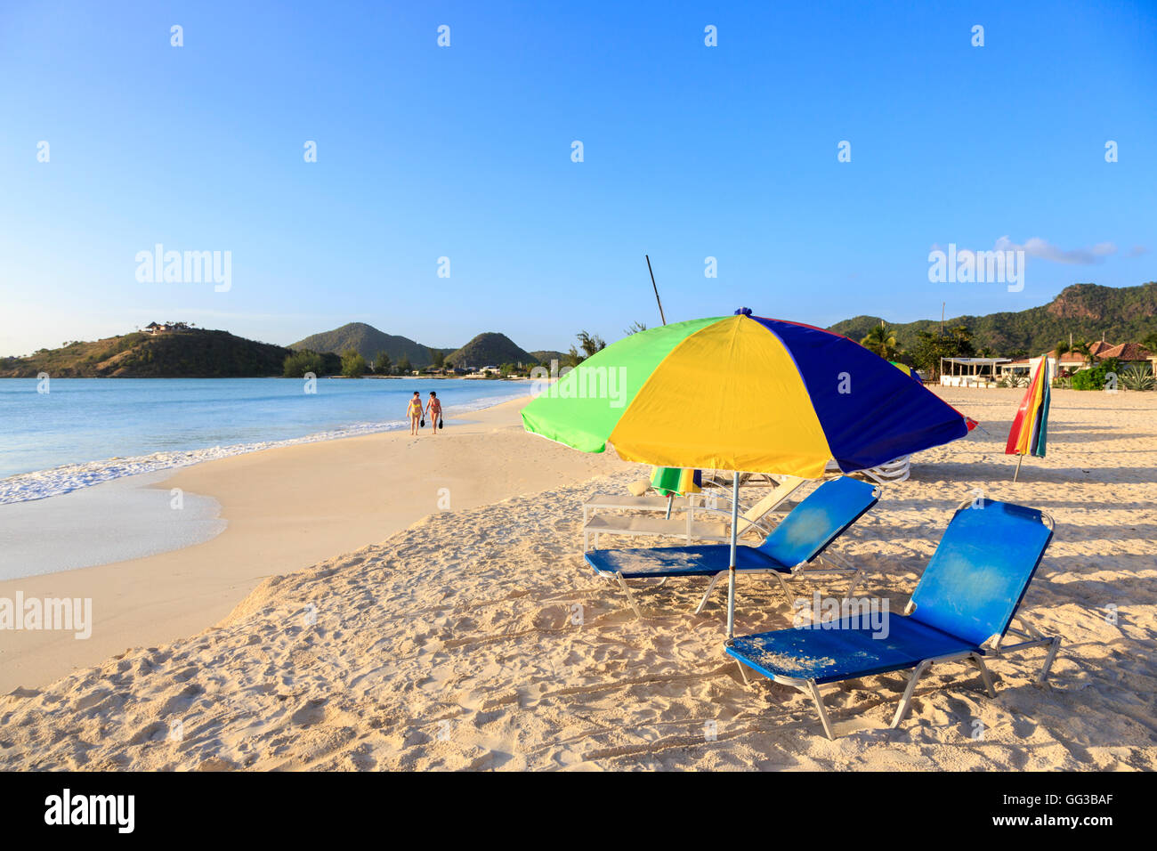 Sun parasol and loungers on golden sand beach at Jolly Harbour, south-west Antigua on a sunny day with blue sky - Stock Image