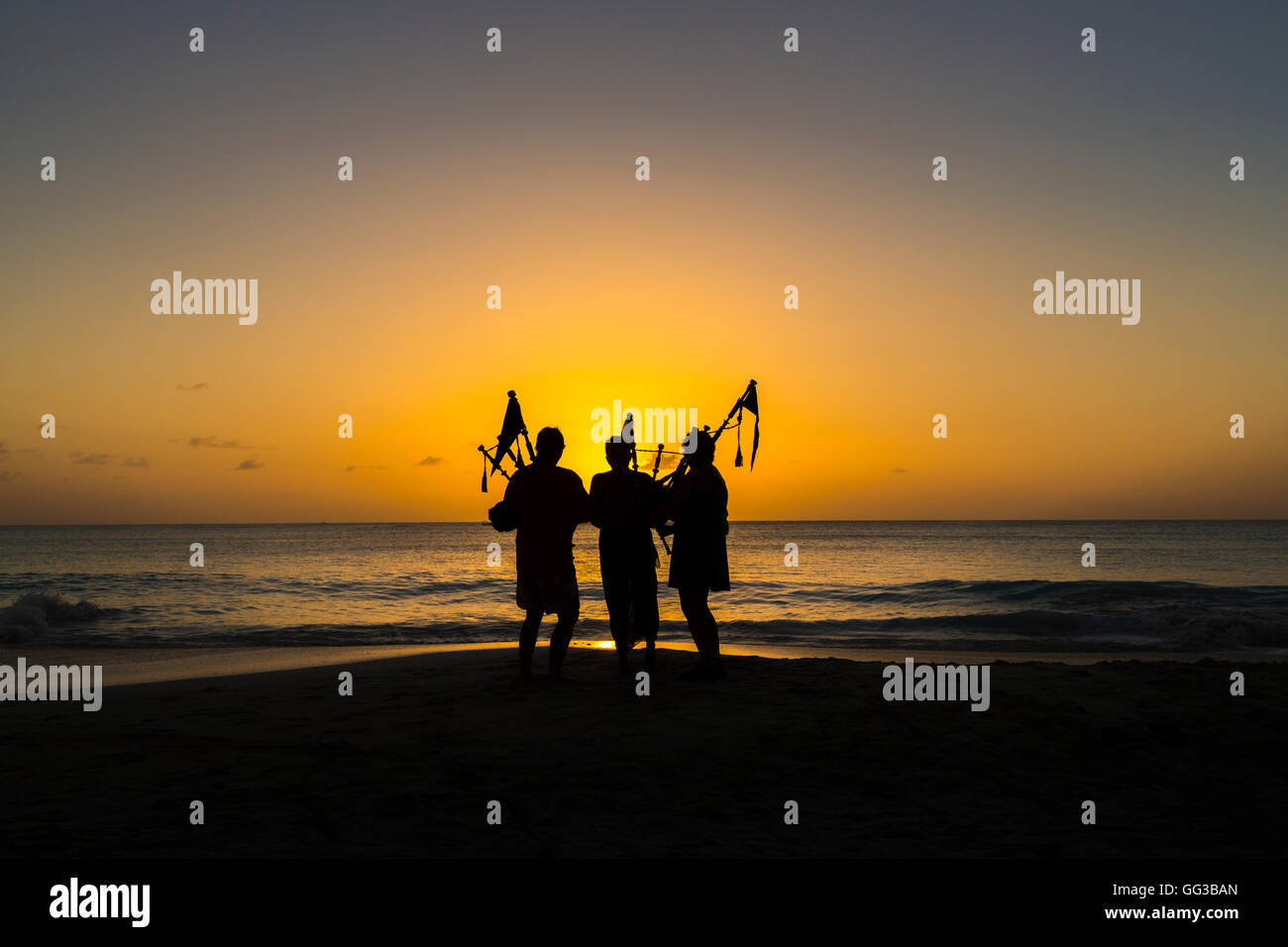 Bagpipers playing bagpipes on the beach at Jolly Harbour at sunset, south-west Antigua - Stock Image