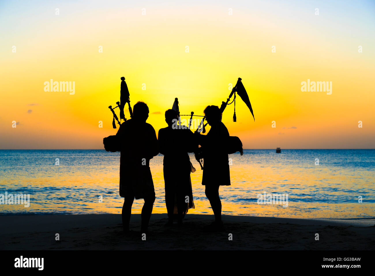 Bagpipers playing bagpipes on the beach at Jolly Harbour at sunset, south-west Antigua Stock Photo