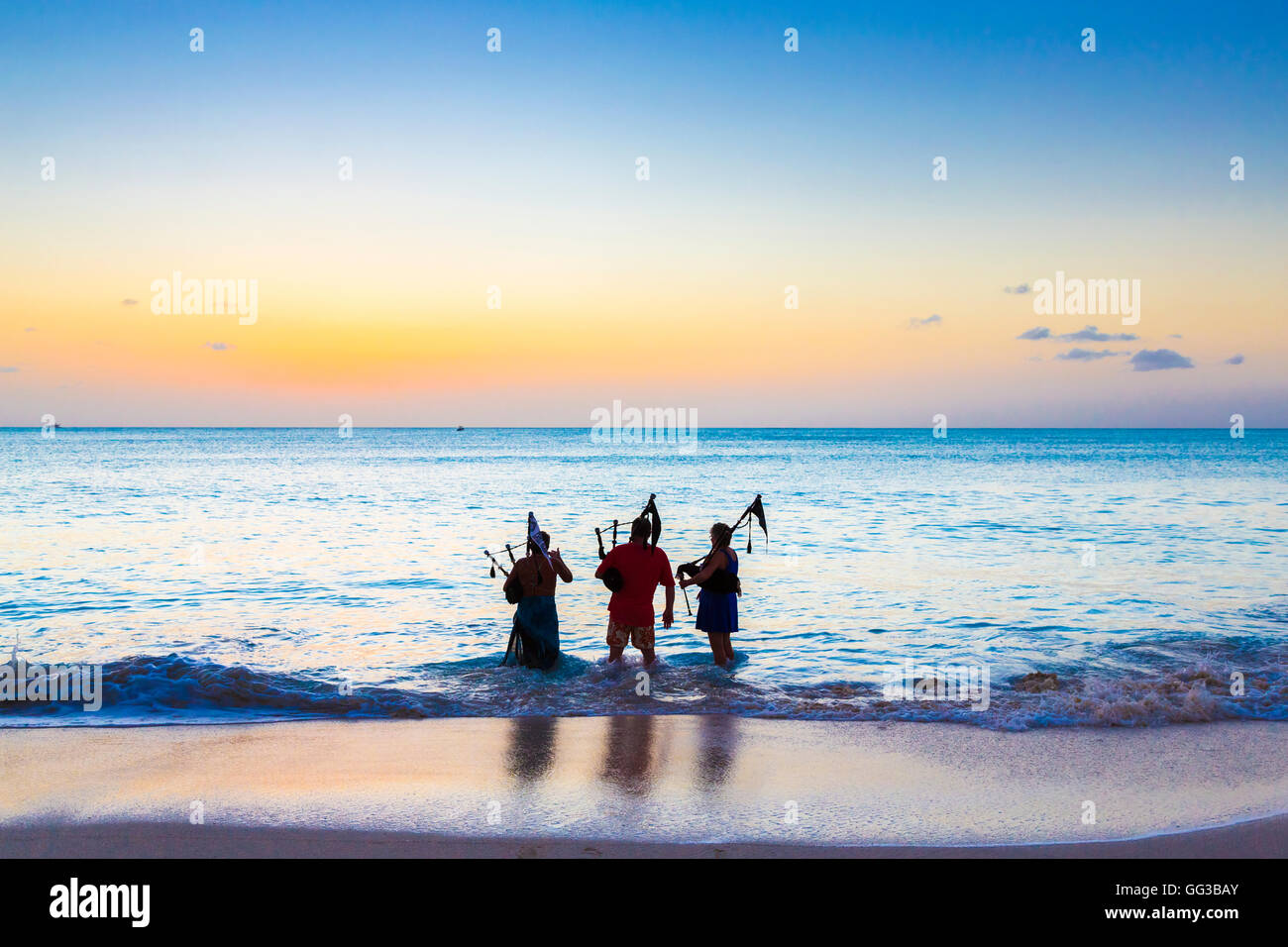 Bagpipers wading into the sea playing bagpipes on the beach at Jolly Harbour at sunset, south-west Antigua - Stock Image
