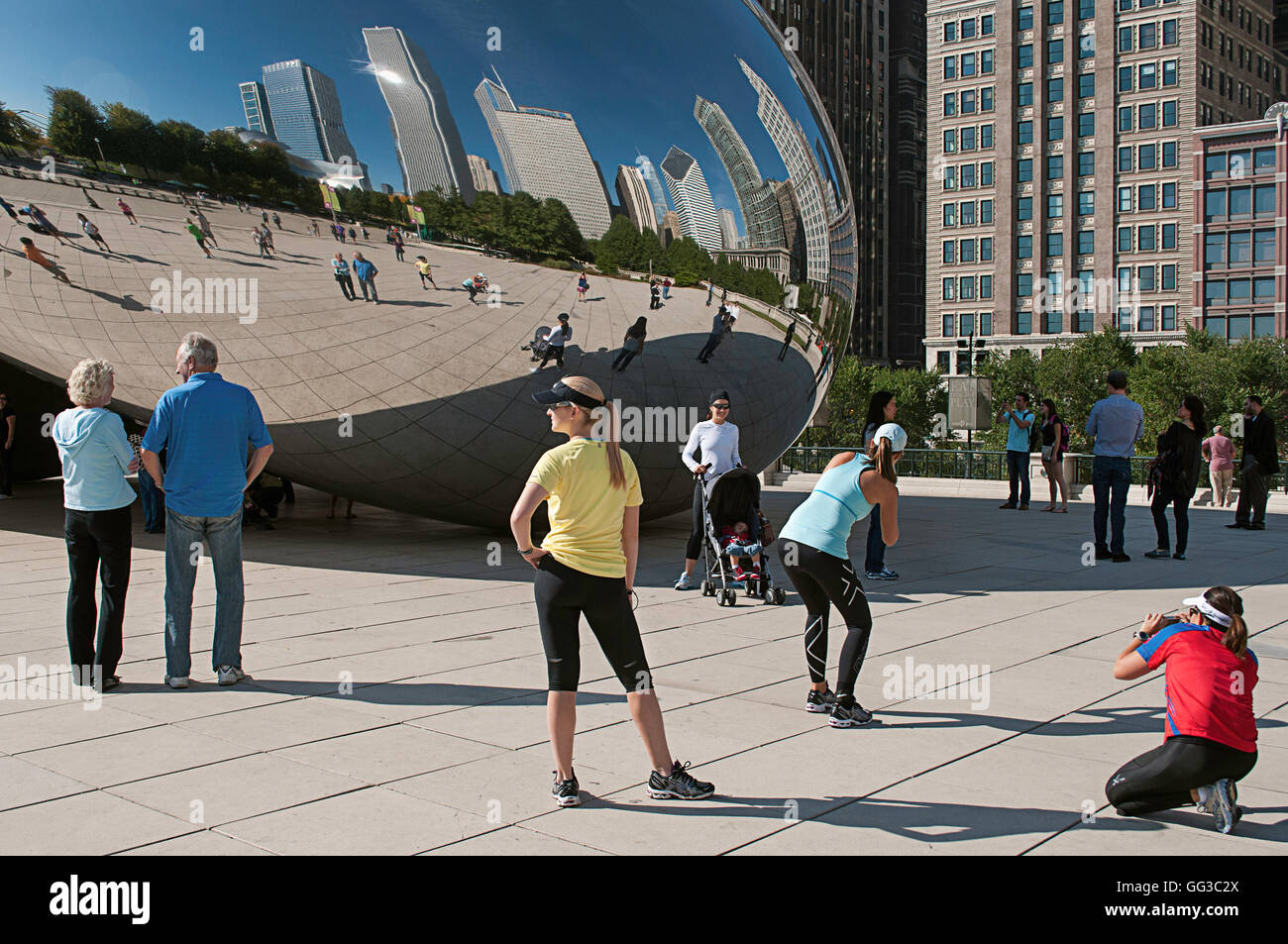 People posing for photos in front of Cloud Gate (the Bean) in Millennium Park, Chicago, Illinois marathon weekend. - Stock Image