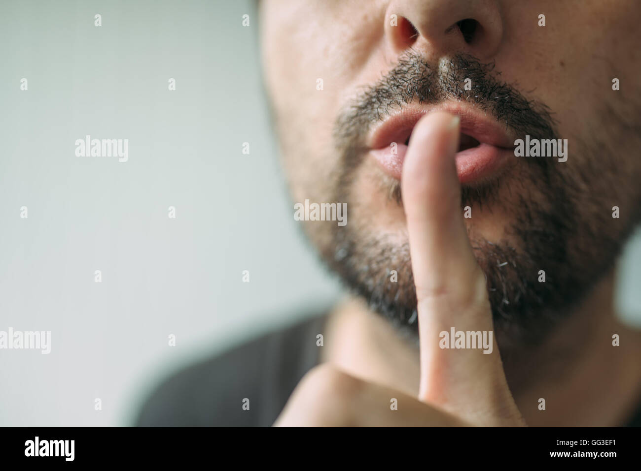 Finger on lips as man gesturing shhh sign, please be silent concept with selective focus - Stock Image