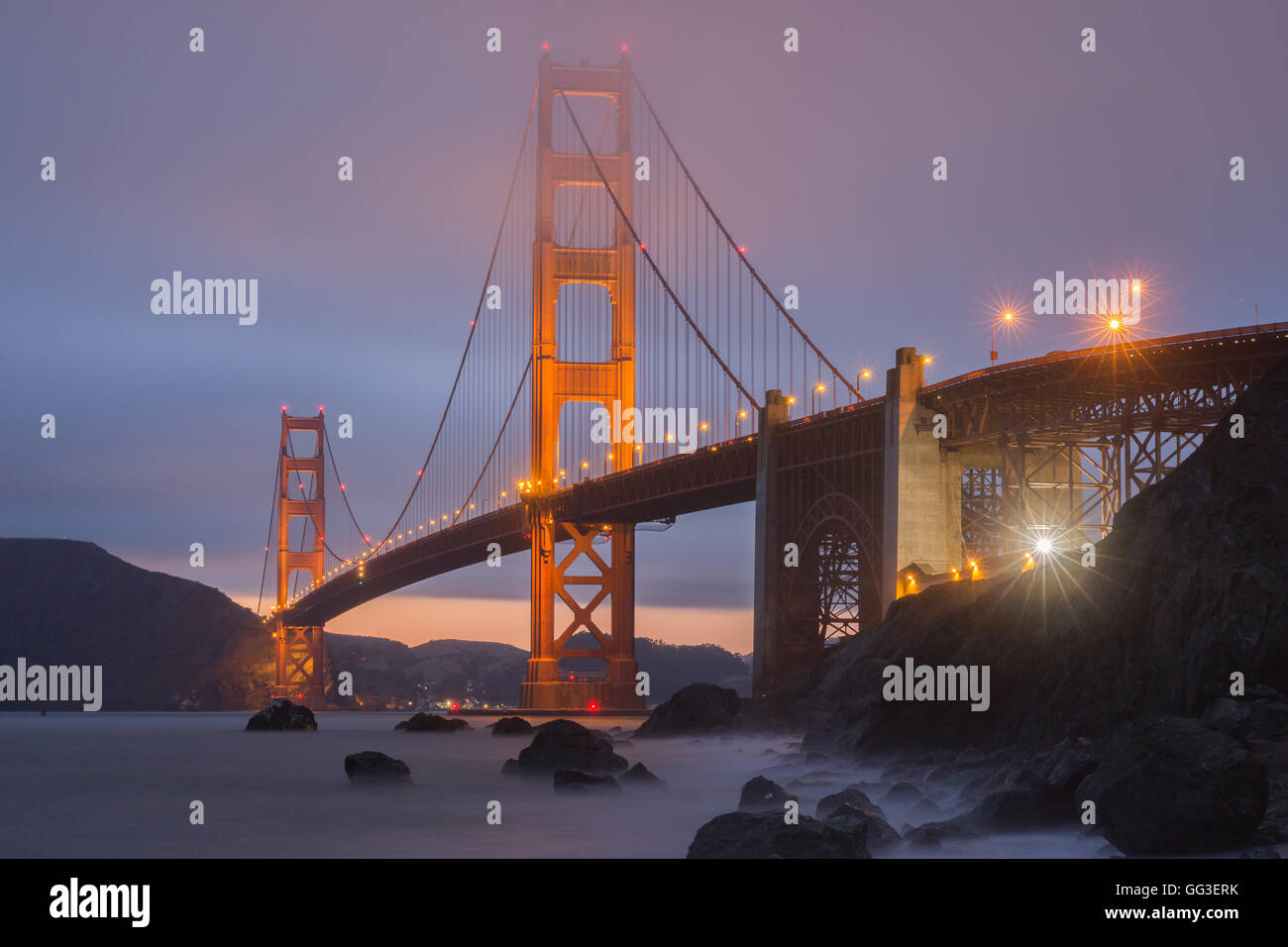 Crack in the clouds behind the Golden Gate Bridge as seen from Marshall's Beach. - Stock Image