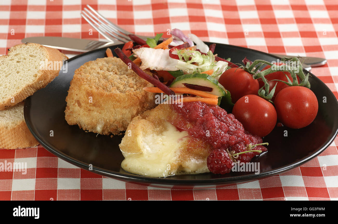 baked breaded camembert with salad and raspberry coulis - Stock Image