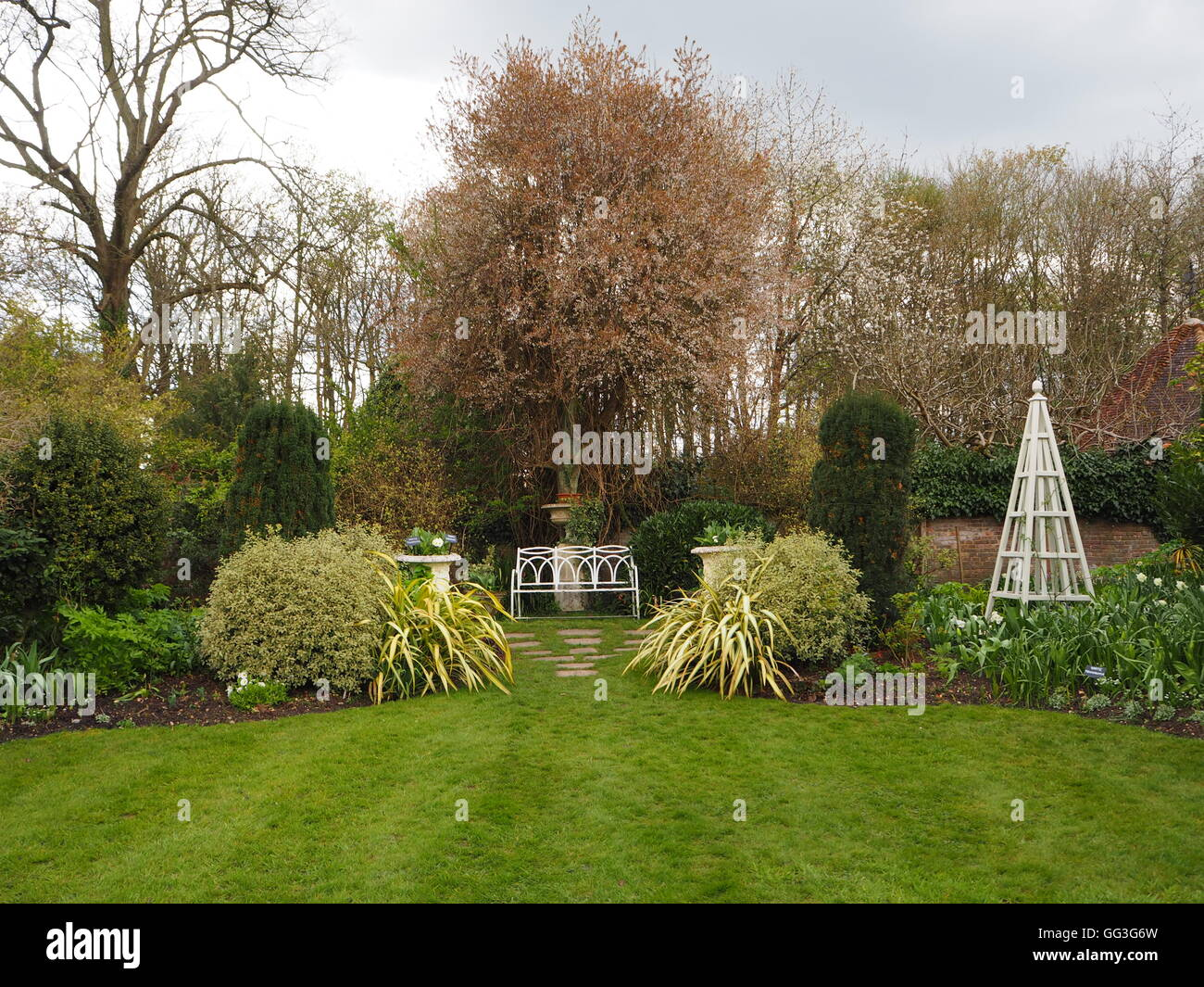 Chenies Manor white garden with lawn, shrubs, variegated greenery, white bench, urns, paving slabs and obelisk in - Stock Image