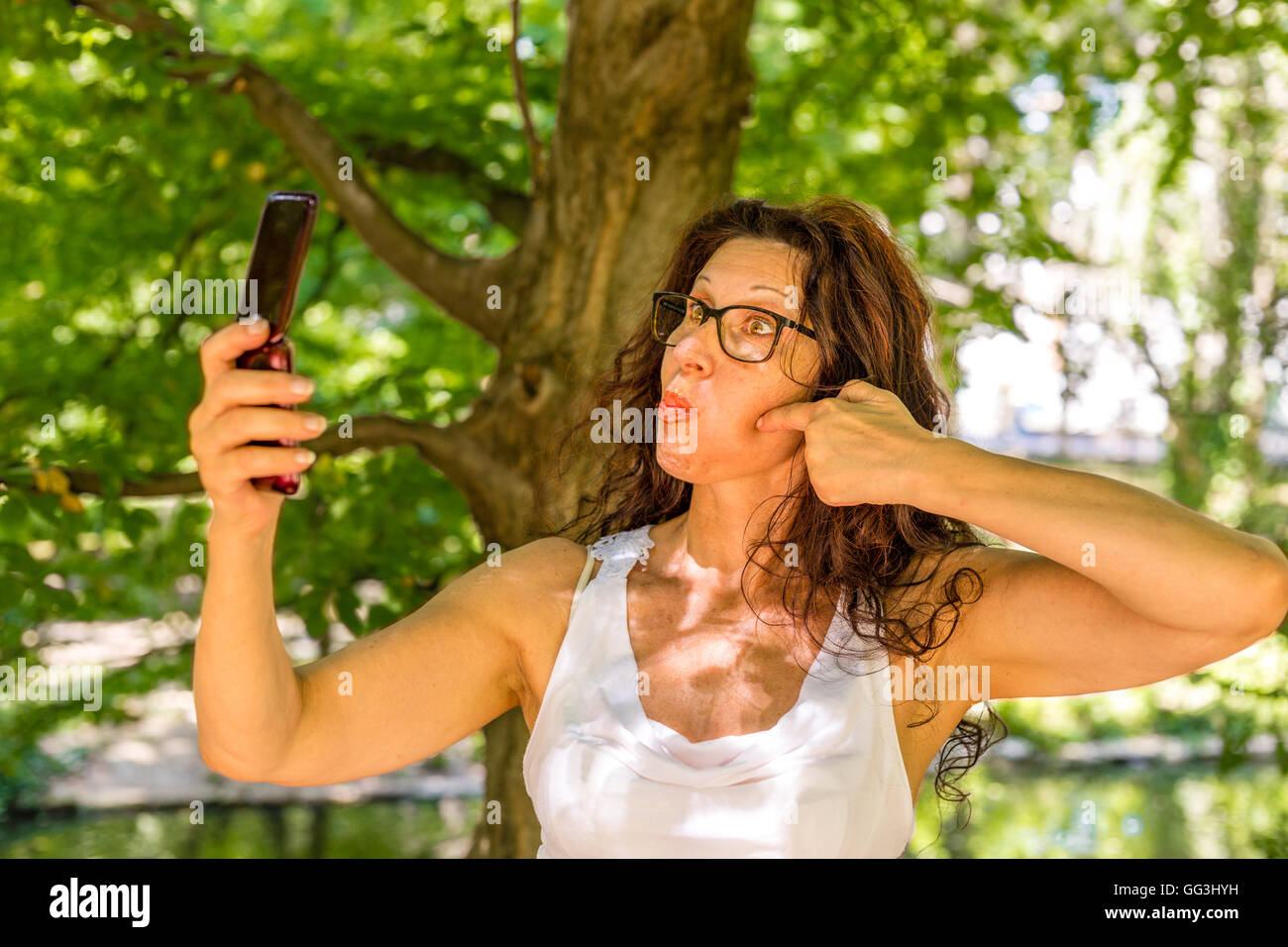 mature woman takes a selfie with a phone for the elderly grimacing - Stock Image
