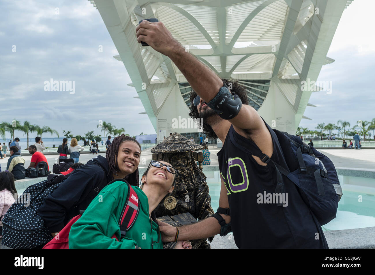 Young people take selfies with a living statue ( mime artist posing for hours in the street like a statue with realistic - Stock Image