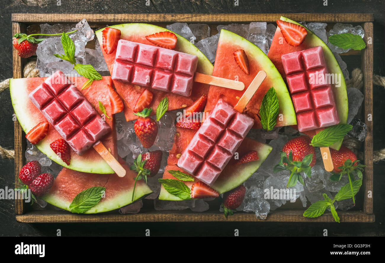 Homemade watermelon strawberry popsicles in wooden tray - Stock Image