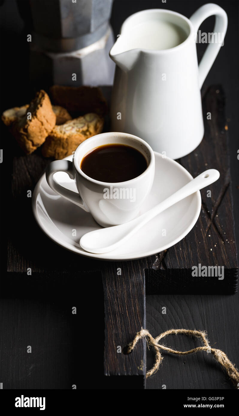 Italian coffee set for breakfast. Cup of hot espresso, creamer with milk, cantucci and moka pot on dark rustic wooden - Stock Image