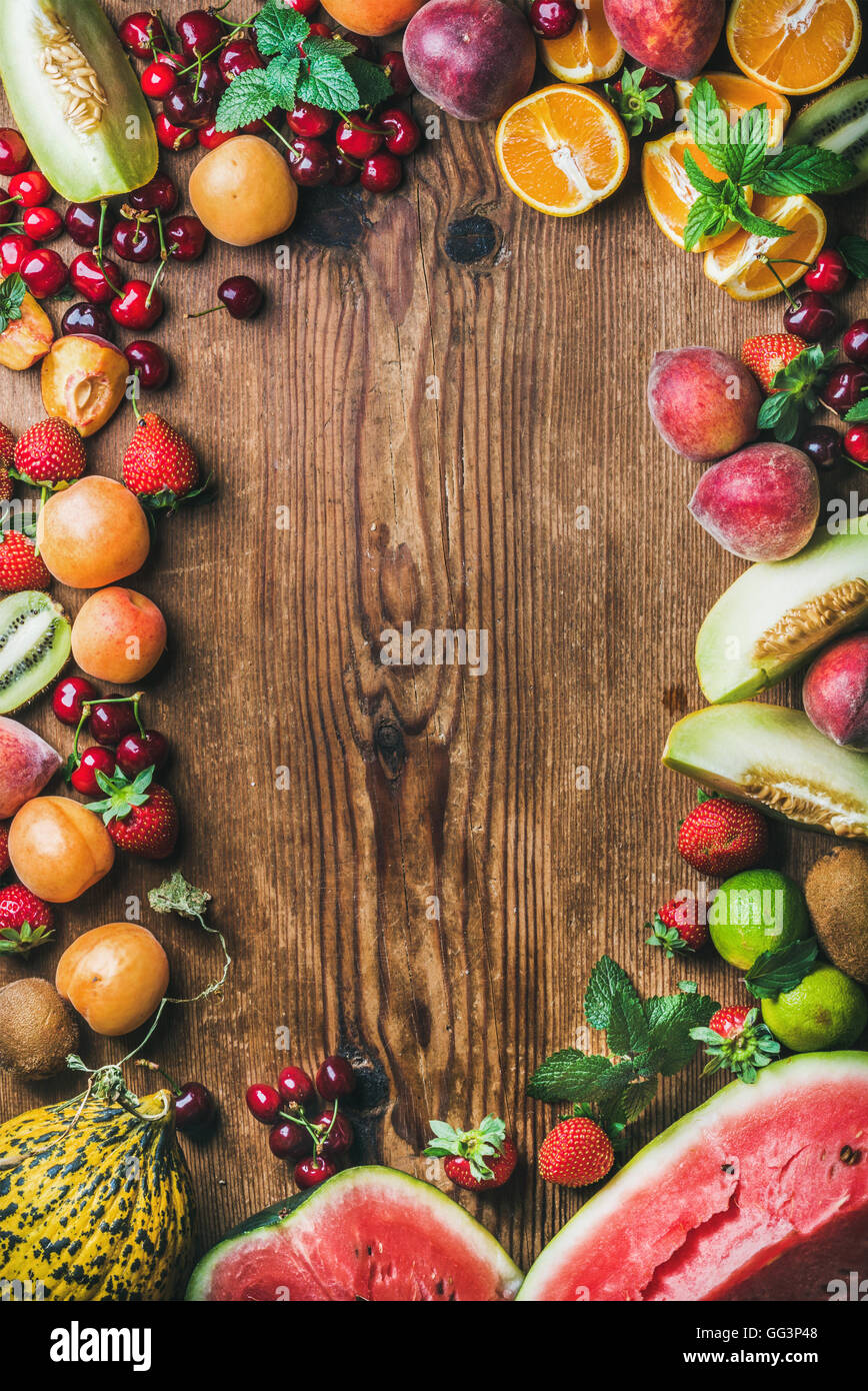 Summer fresh fruit variety over rustic wooden background - Stock Image