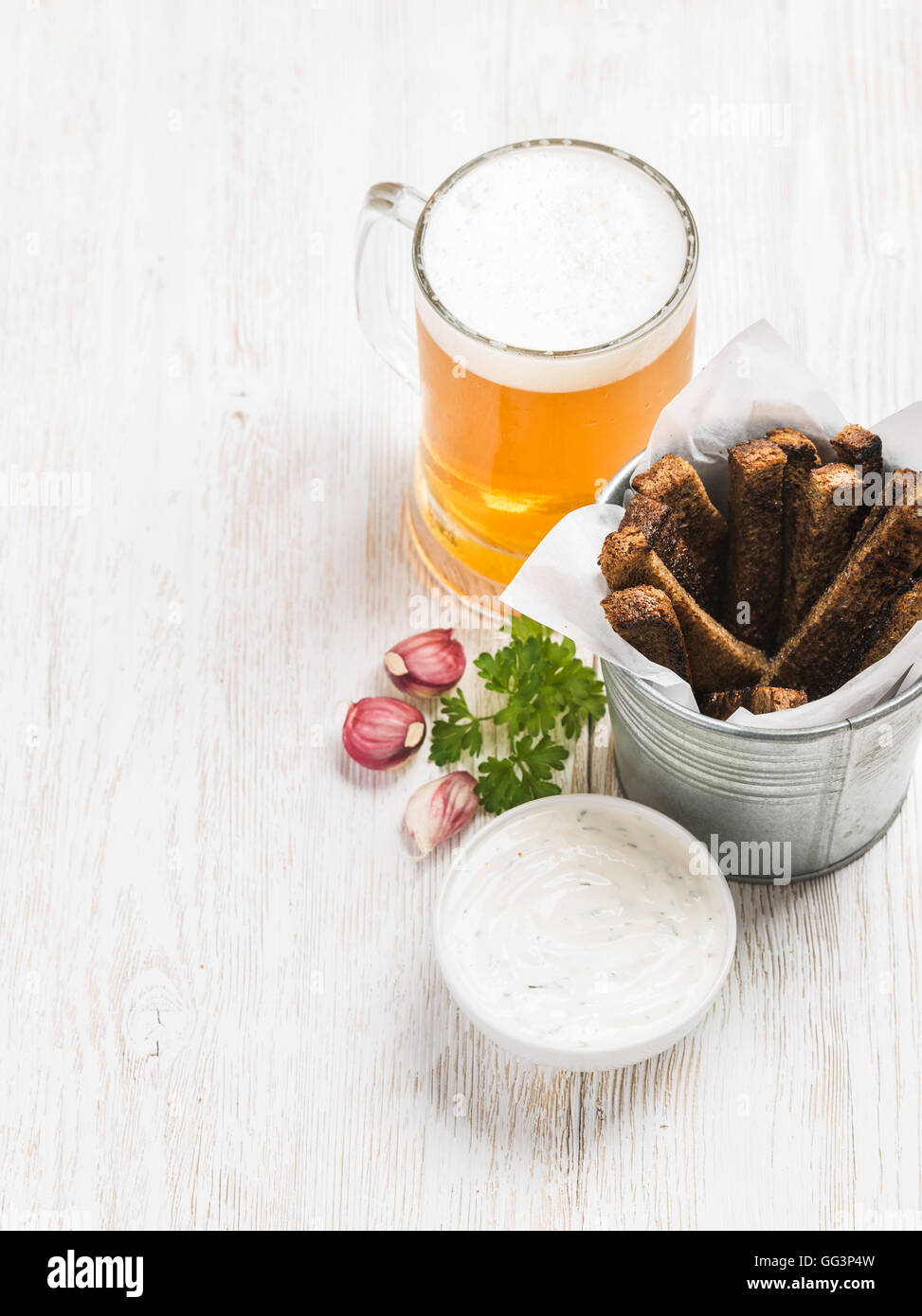 Beer snack set. Pint of pilsener in tall mug and rye bread croutons with garlic cream cheese sauce over white painted - Stock Image