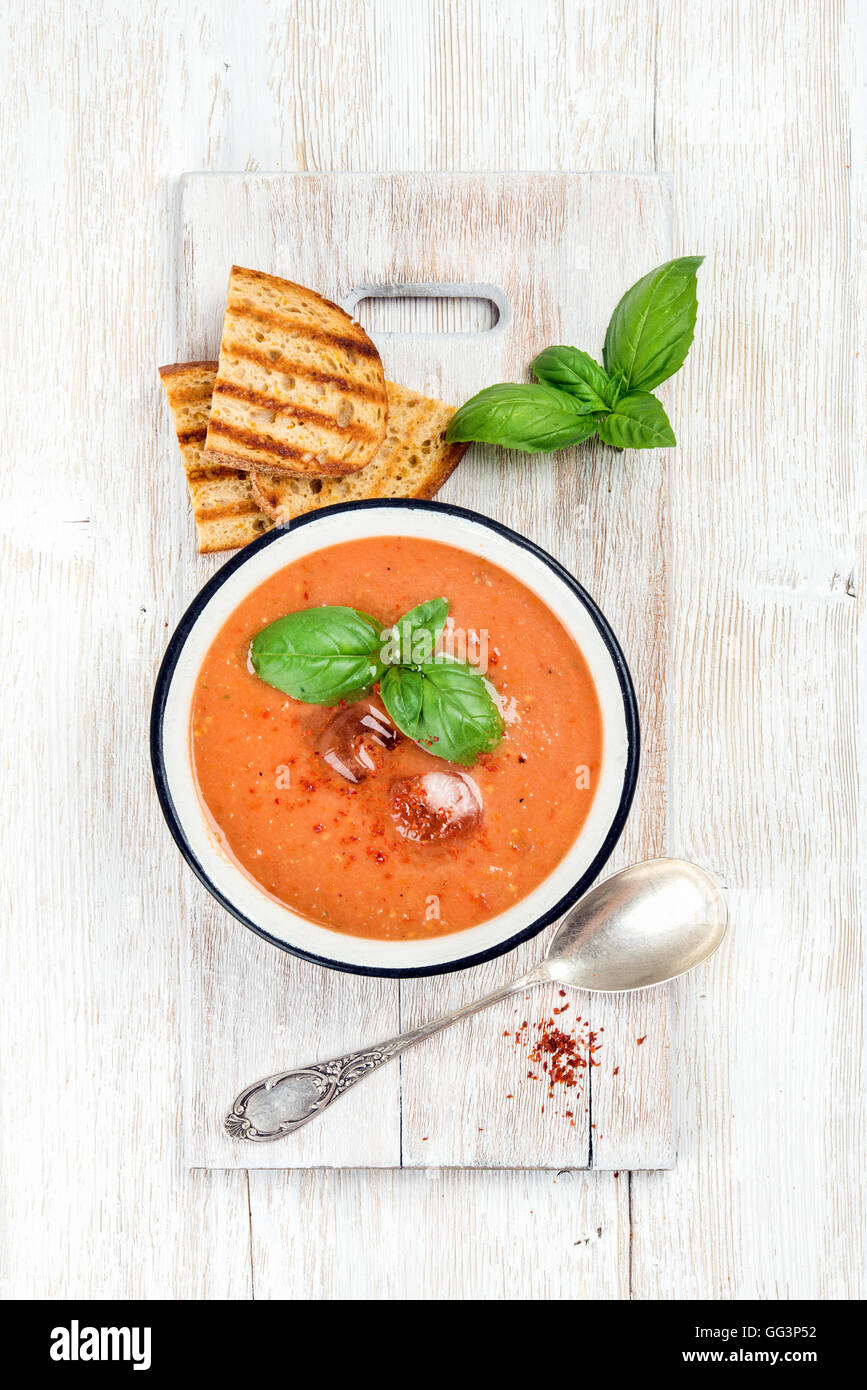 Cold gazpacho soup with ice and basil over white background - Stock Image