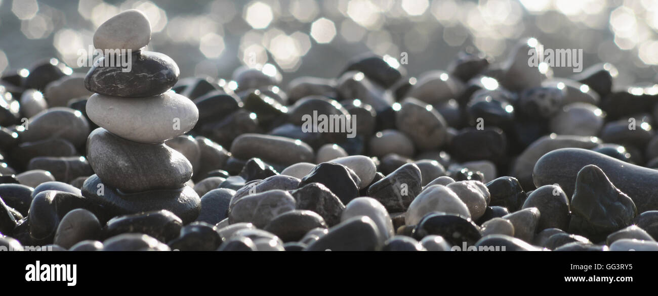 balancing stone tower on the beach - Stock Image