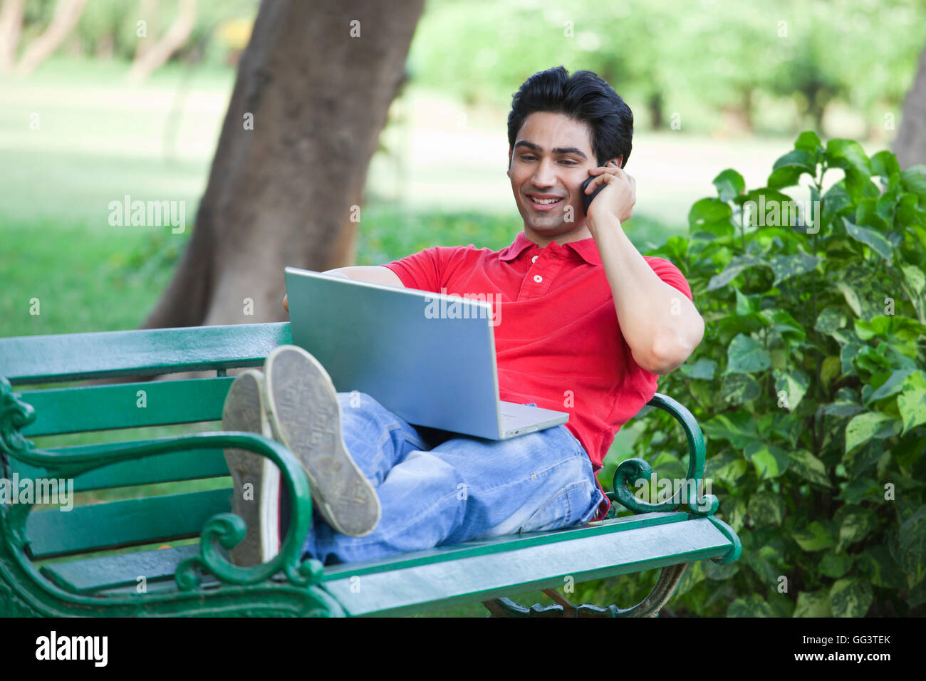 Young man on the cal while using laptop - Stock Image