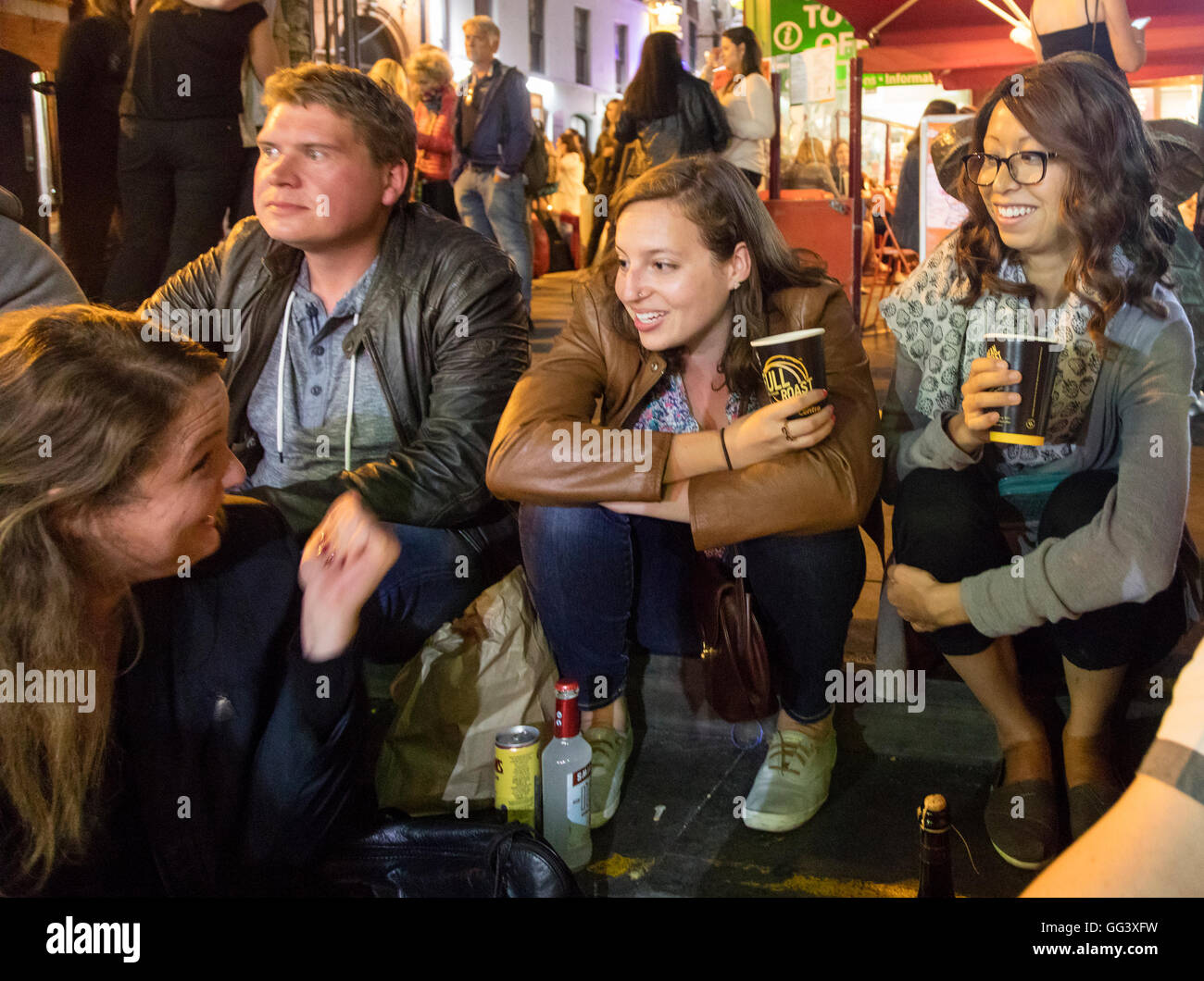 youths sitting on steps drinking at night in Temple Bar, Dublin, Ireland - Stock Image