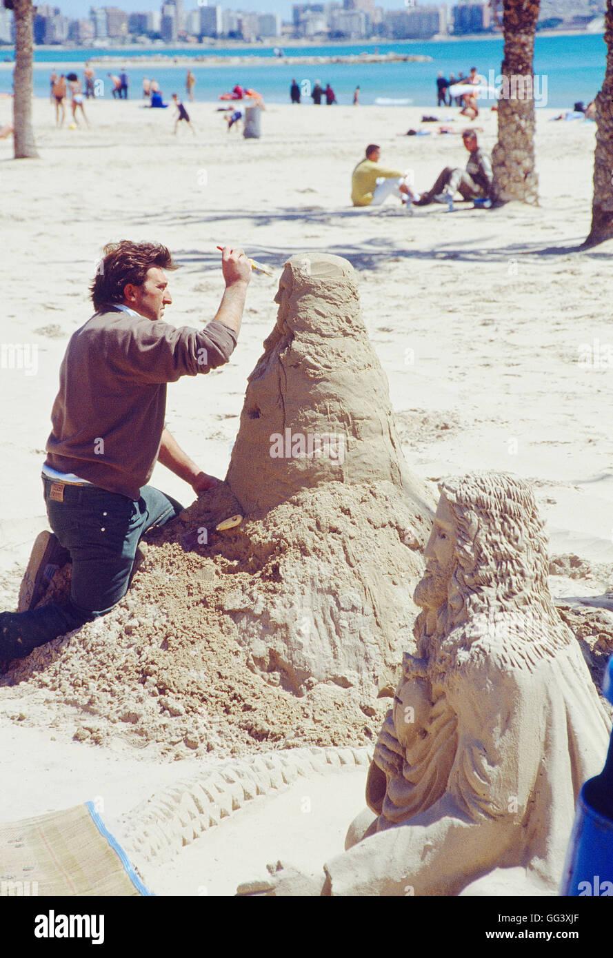 Sand sculptor working. El Postiguet beach, Alicante, Comunidad Valenciana, Spain. - Stock Image