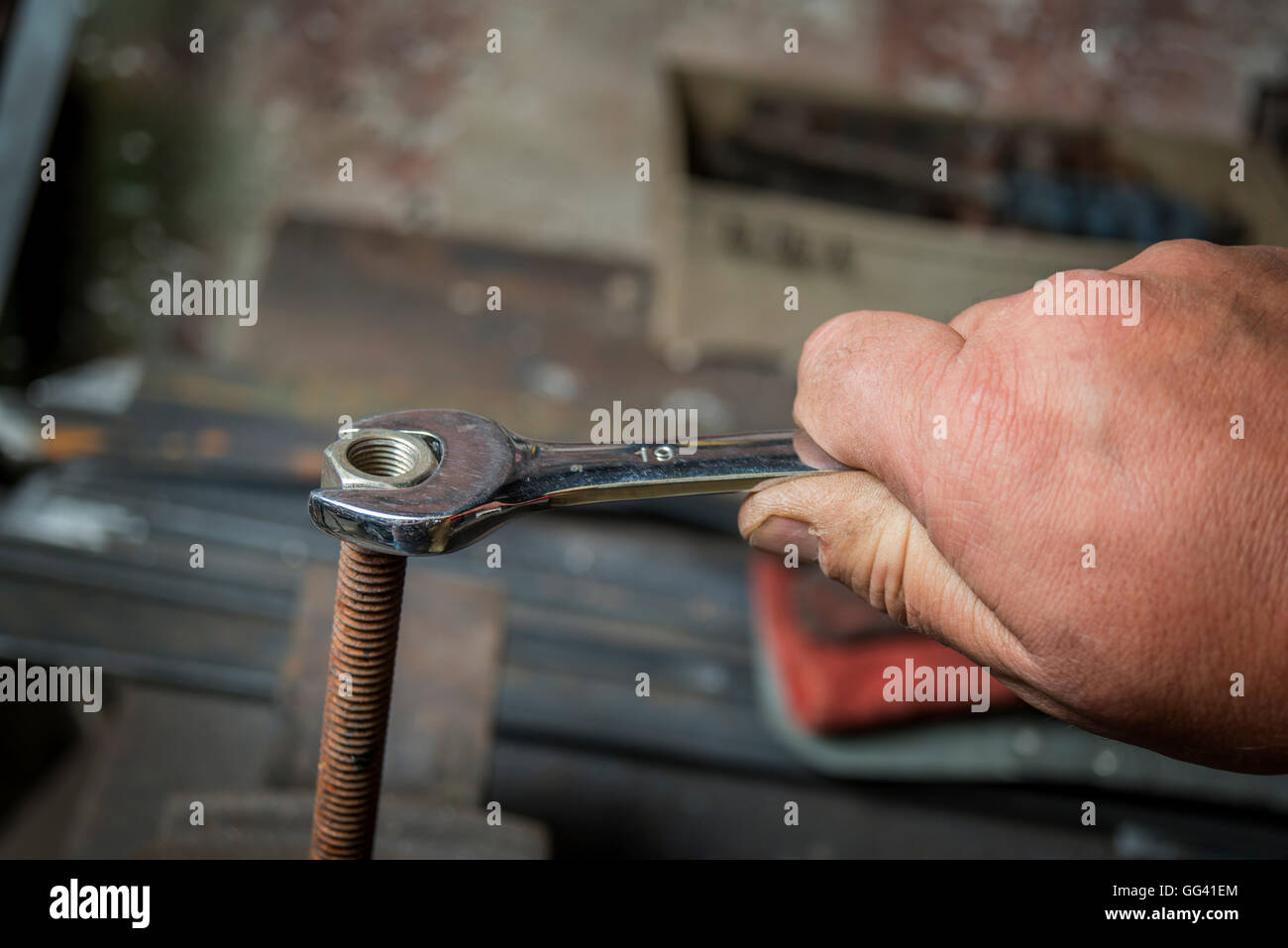 worker hand tightening or loosening a nut of a rusty bolt with a wrench on white background - Stock Image