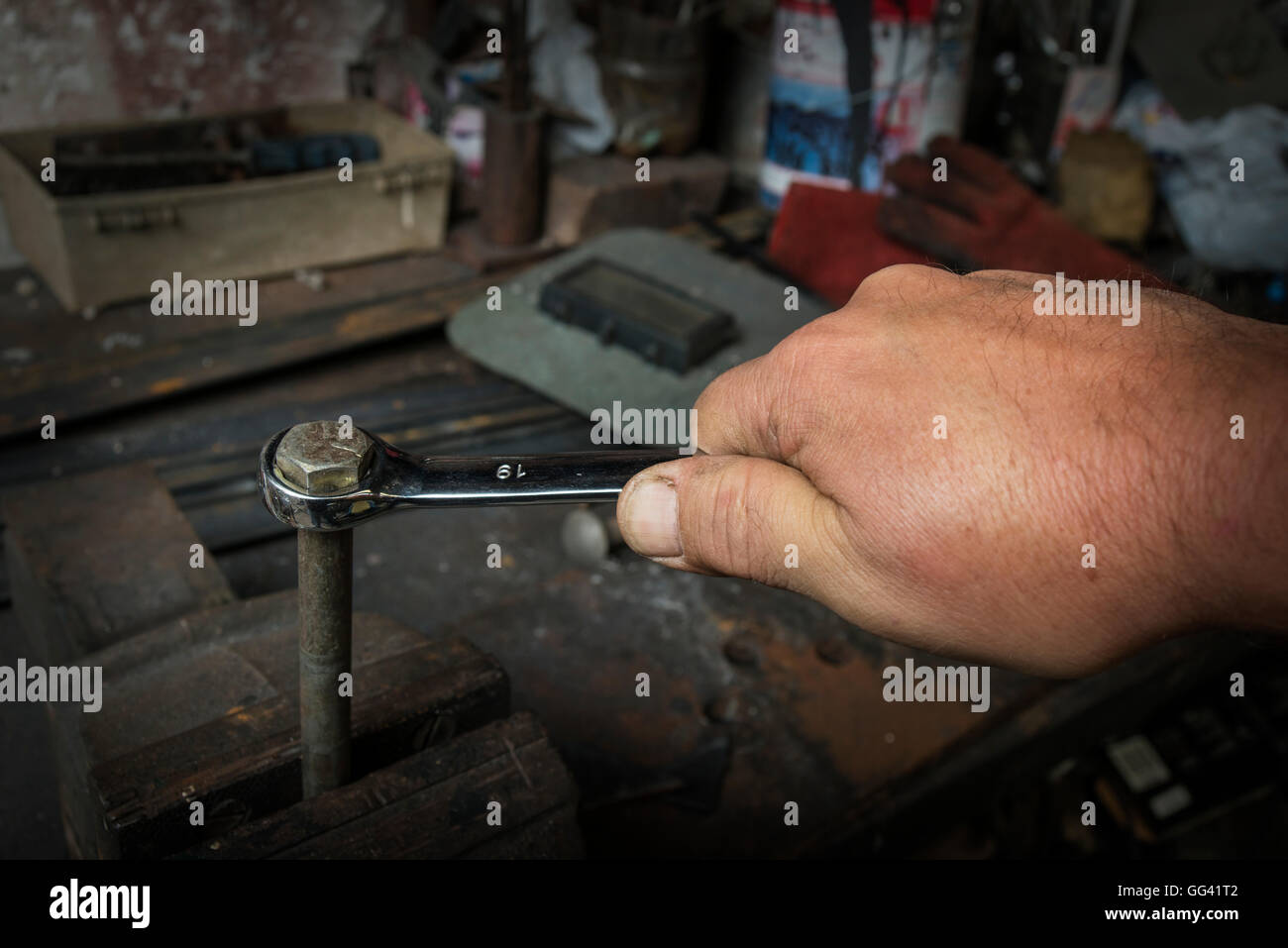 worker hand tightening or loosening a nut of a rusty bolt with a wrench - Stock Image