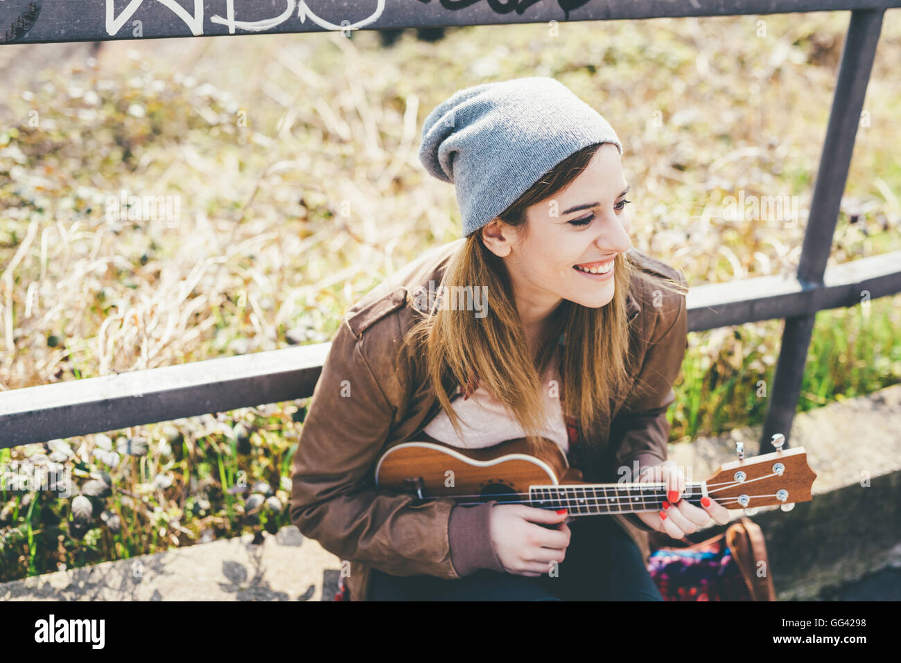 Half length of young beautiful caucasian woman outdoor in the city playing ukulele overlooking smiling - musician, - Stock Image