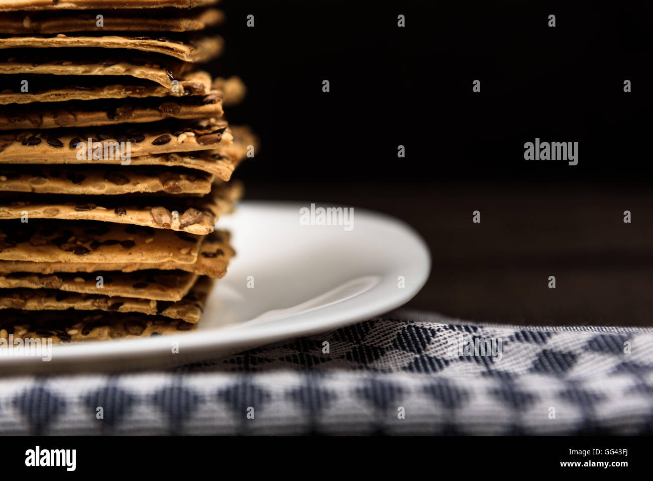 cookies with sunflower seeds and sesame seeds on a white plate with checkered napkin - Stock Image