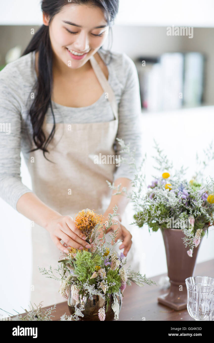 Young Chinese woman arranging flowers at home - Stock Image