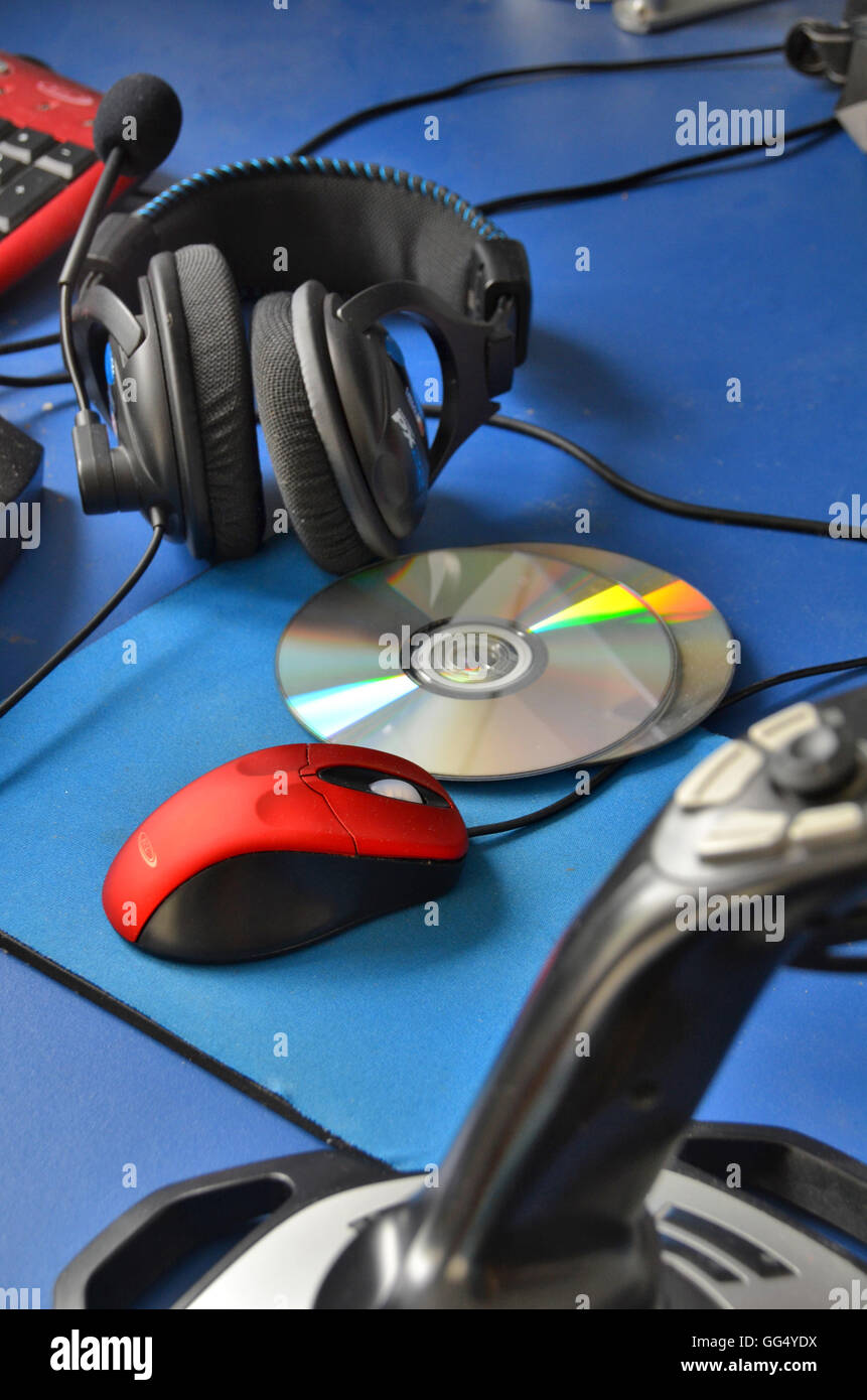 Computer desktop with gaming accessories including  headphones, DVDs, joystick, red mouse and mat. - Stock Image