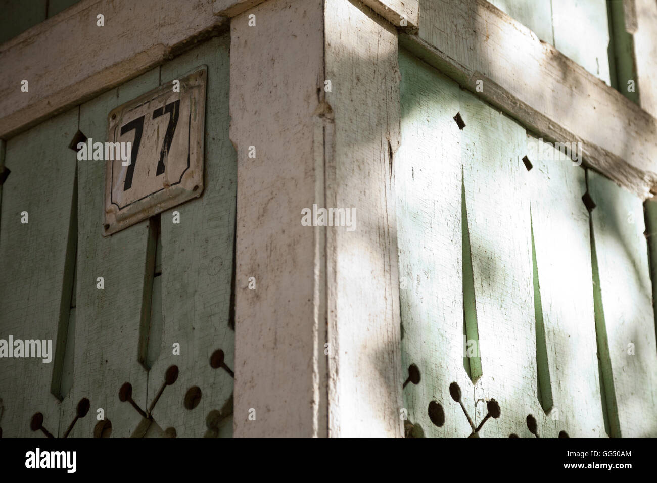 Traditional Russian wooden house with number plate close-up. Wood carved decorations on a green rustic building - Stock Image
