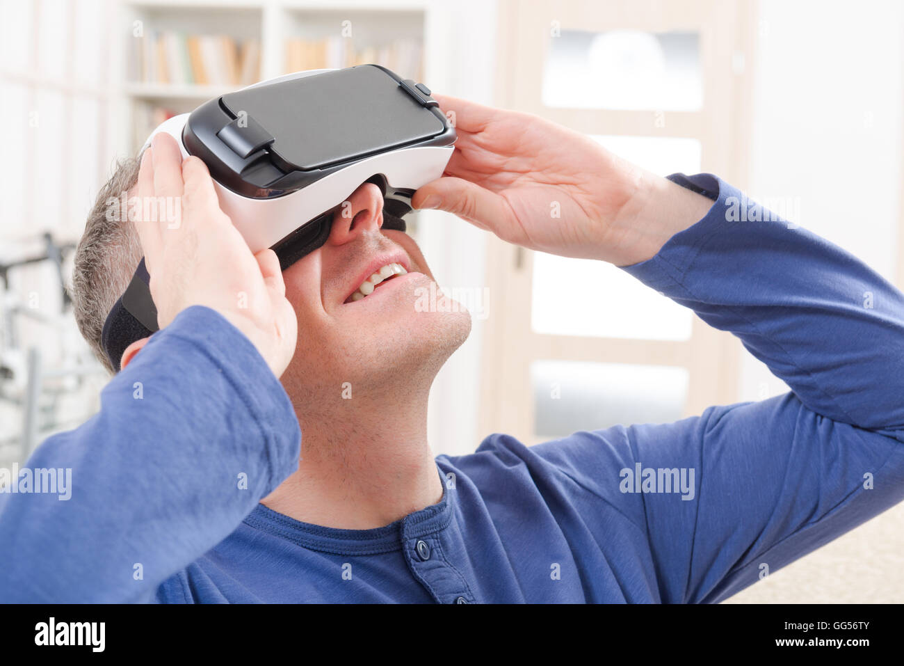 Man using virtual reality headset at home - Stock Image